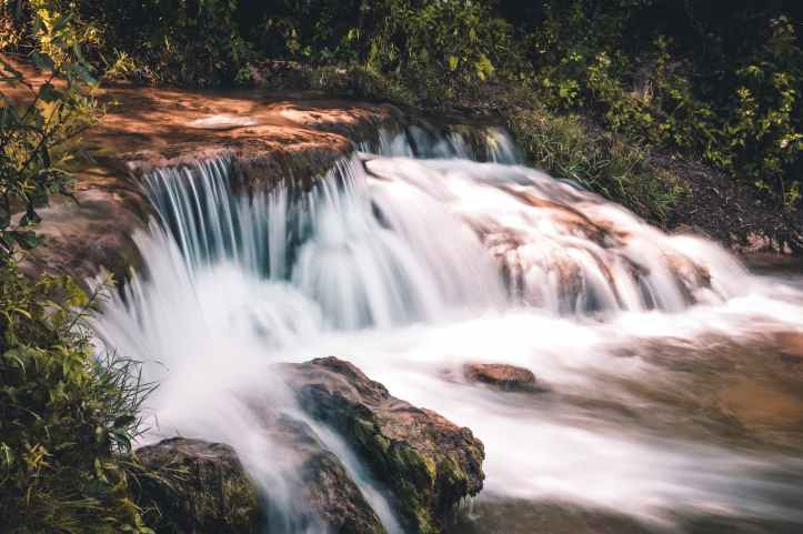 time lapse photo of waterfall surrounded by grass