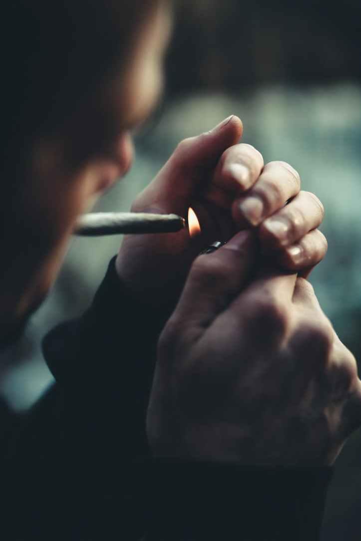 selective focus photography of man lighting cigarette
